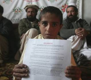 The son of Hafizullah Shahbaz Khiel, who has been held since last September at Bagram Air Base, Afghanistan, as a US prisoner, holds up papers declaring his innocence. (Photo: Rafiq Maqbool / AP)